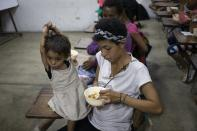 In this Feb. 27, 2020 photo, a mother feeds her daughter rice mixed with meat and vegetables at a soup kitchen in The Cemetery slum in Caracas, Venezuela. According to a survey recently published by the U.N. World Food Program, one of every three Venezuelans cope with food insecurity, unable to get enough food to meet their basic dietary needs. (AP Photo/Ariana Cubillos)