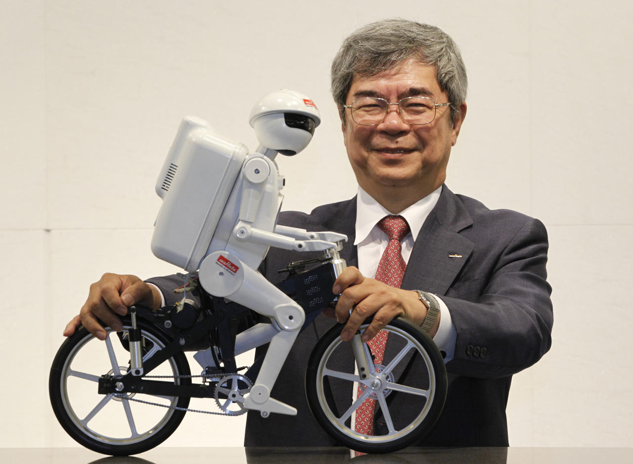 "Murata Manufacturing Co Ltd President Tsuneo Murata poses with his company's bicycle-riding robot ""Murata Seisaku-kun"" after an interview with Reuters on the sidelines of CEATEC JAPAN 2012 electronics show in Chiba, east of Tokyo, October 2, 2012. Anti-Japanese sentiment in China, falling prices and growing competition from a South Korean rival are just a few of the challenges faced by Murata, which supplies Apple Inc with components for its iPhone 5. But even with those challenges, Murata, said on Tuesday the company is forecasting stronger demand from smartphone makers in the July to September quarter and that its factories were operating at full capacity. To match Interview MURATA-INTERVIEW/ REUTERS/Yuriko Nakao (JAPAN - Tags: TRANSPORT BUSINESS EMPLOYMENT)"