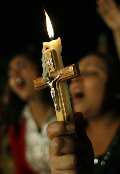 FILE - In this Sunday, Oct. 16, 2011 file photo, Egyptian Copts carry a Christian cross and a candle and chant prayers while taking part in a protest marking one week since deadly clashes between Coptic protesters and the military, in Cairo, Egypt. Egypt's estimated 8 million Coptic Christians are feeling increasingly cornered amid the rise to power of hardline Islamists after the ouster of Hosni Mubarak's longtime authoritarian regime and fear that they will bear the brunt of blame for the film that mocked the Prophet Muhammad. (AP Photo/Nasser Nasser)