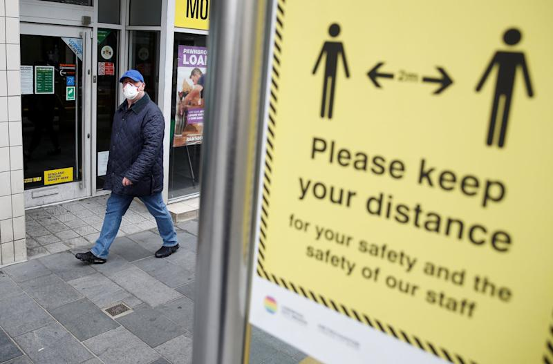 A man wearing a face mask walks by a social distance sign in Liverpool: REUTERS