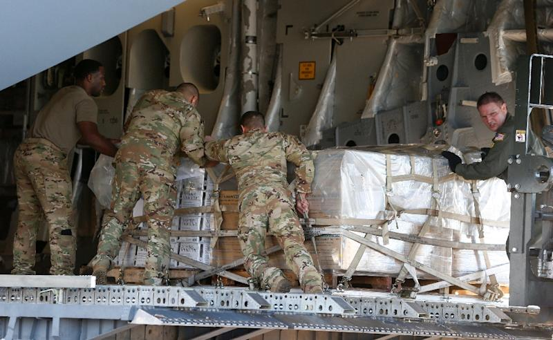 US soldiers load a C-17 cargo plane with food, water and medicine for a humanitarian mission to Venezuela, at Homestead Air Force Base in Florida, on February 22, 2019 (AFP Photo/RHONA WISE)