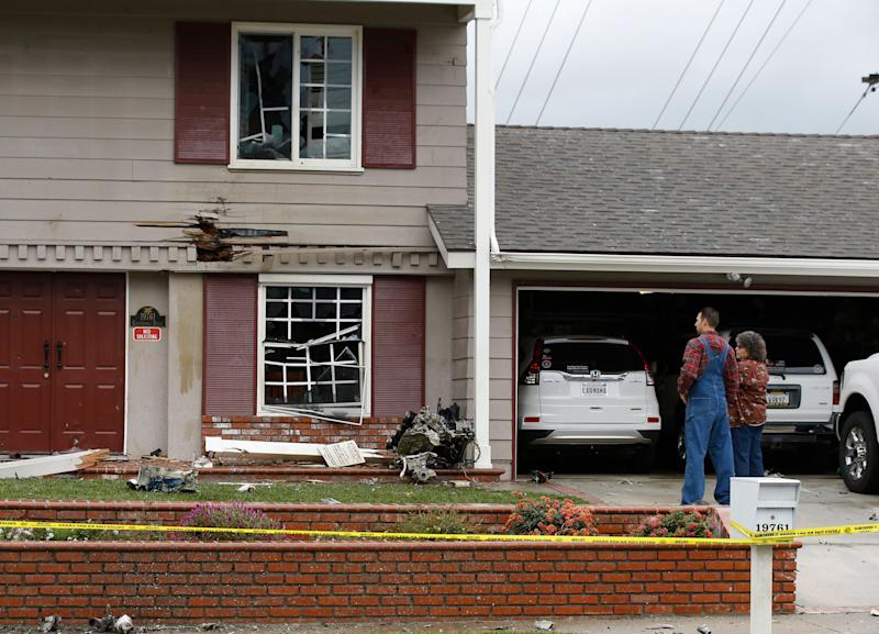 Residents look at the debris that hit their home after a small plane crashed into the residential neighborhood of Yorba Linda, Calif., Feb. 3, 2019. (Photo: Alex Gallardo/AP)