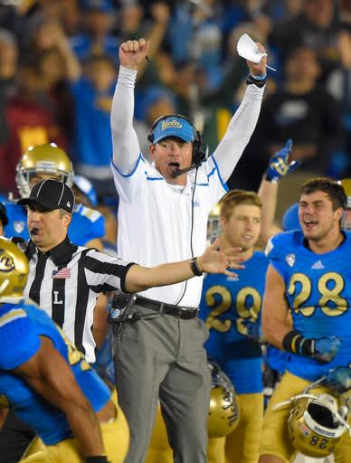 UCLA coach Jim Mora celebrates after UCLA intercepted a pass during the first half of an NCAA college football game against Southern California, Saturday, Nov. 22, 2014, in Pasadena, Calif. (AP Photo/Mark J. Terrill)