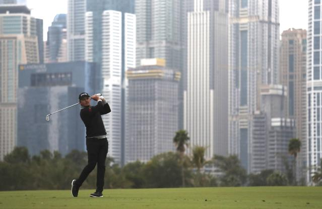 England's Eddie Pepperell follows his ball on the 13th fairway during the second round of the Dubai Desert Classic golf tournament in Dubai, United Arab Emirates, Friday, Jan. 24, 2020. (AP Photo/Kamran Jebreili)