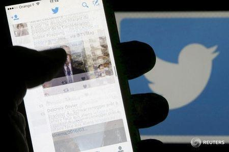A man reads tweets on his phone in front of a displayed Twitter logo in Bordeaux, southwestern France, March 10, 2016. REUTERS/Regis Duvignau/Illustration