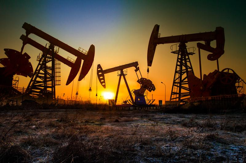Pumps in an oil field at sunset
