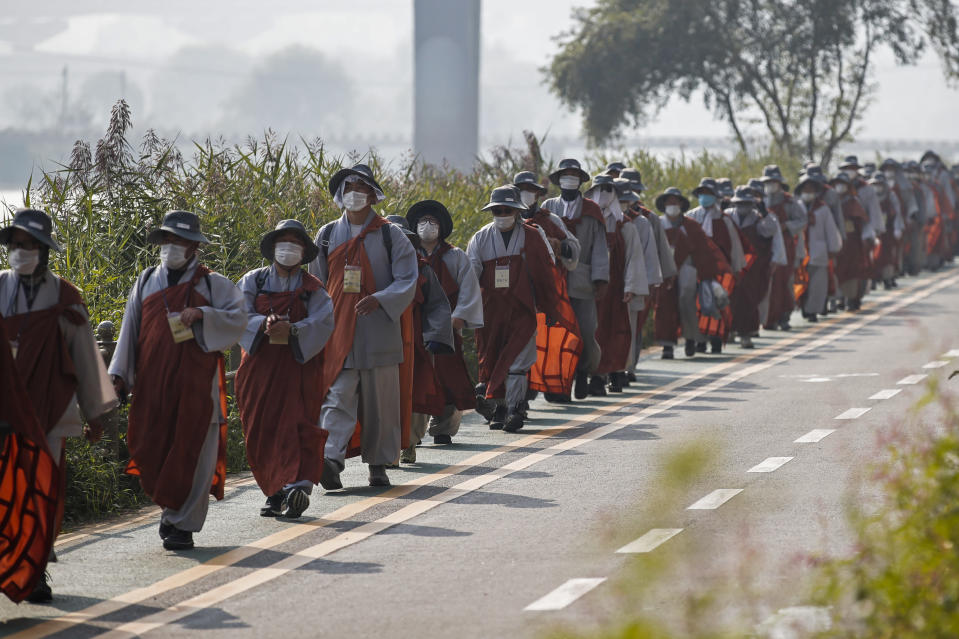 Buddhist monks and believers walk along a stream in Seoul, South Korea, Tuesday, Oct. 27, 2020. About 100 monks and followers marched the 500 kilometer (310 mile) pilgrimage to pray for the country to overcome the coronavirus. (AP Photo/Lee Jin-man)