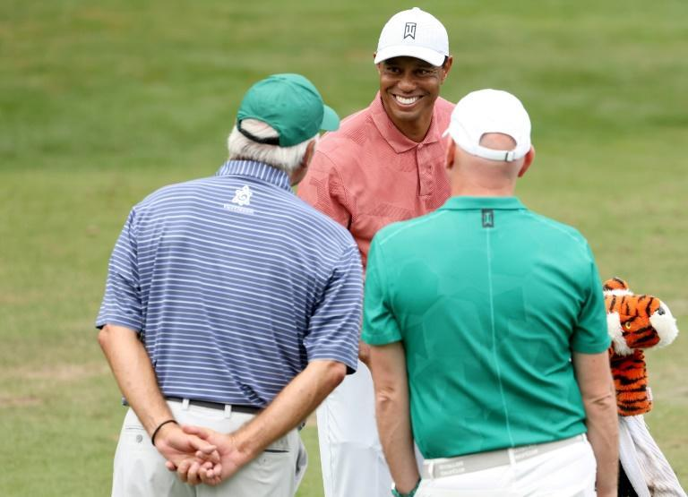 Defending Masters champion Tiger Woods chats with fellow Masters winner Fred Couples (L) and caddie Joe LaCava during a practice round before Thursday's start of the 84th Masters