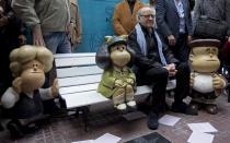 """FILE - In this Sept. 29, 2014 file photo, Argentine cartoonist Joaquin Salvador Lavado, better known as """"Quino,"""" who created the comic strip Mafalda, poses for a photo with statues of the strip's characters, Susanita, left, Mafalda, center, and Manolito, during a 50th-anniversary celebration in Buenos Aires, Argentina. Lavado passed away on Wednesday, Sept. 30, 2020, according to his editor Daniel Divinsky who announced it on social media. (AP Photo/Eduardo Di Baia, File)"""