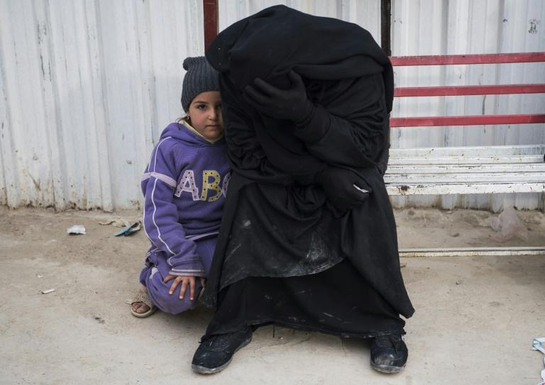 A Syrian woman and child wait at a camp for internally displaced people in al-Hol in northeastern Syria