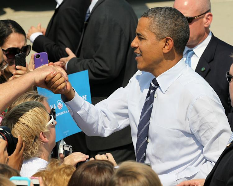 President Barack Obama greets visitors, Tuesday, Aug. 28, 2012, at the Des Moines International Airport in Des Moines, Iowa. (AP Photo/Chris Donahue)