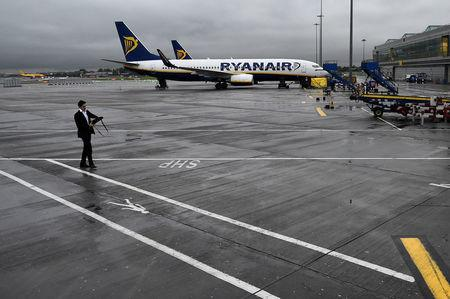 FILE PHOTO - A man walks past a Ryanair aeroplane at Stansted airport in London