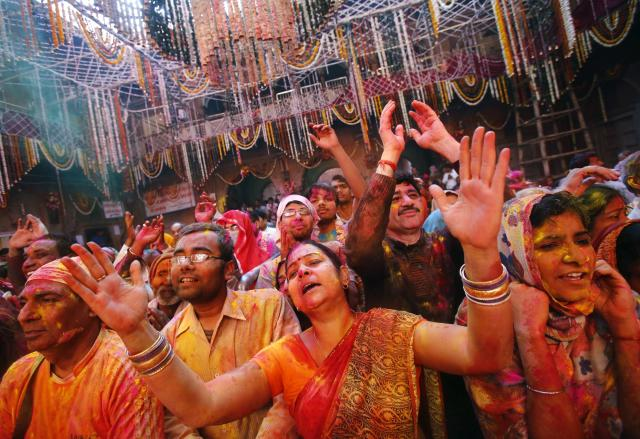 Hindu devotees daubed in colours sing hymns during Holi celebrations at the Bankey Bihari temple in Vrindavan, in the northern Indian state of Uttar Pradesh, March 13, 2014. Holi, also known as the Festival of Colours, heralds the beginning of spring and is celebrated all over India. REUTERS/Anindito Mukherjee (INDIA - Tags: SOCIETY RELIGION)