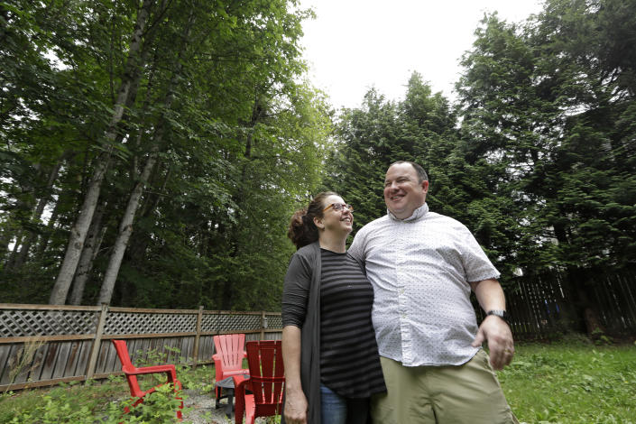 In this photo taken Friday, Aug. 2, 2019, Amy and Jason Ritchie stand in the backyard of their home, adjacent to a forest of conifer and deciduous trees towering overhead, in Sammamish, Wash. The Ritchie's had a fire in the woods behind their property four years ago, which drove home the risks of their neighborhood with houses built steps from the woods' edge but only two main routes out. (AP Photo/Elaine Thompson)