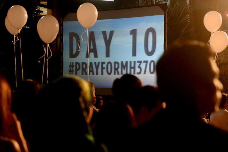 Visitors are silhouetted against a slideshow of best wishes for the missing Malaysia Airline, MH370, during an event at a shopping mall, in Petaling Jaya, on the outskirts of Kuala Lumpur, Malaysia, Tuesday, March 18, 2014. A coalition of 26 countries, including Thailand, are looking for Malaysia Airlines Flight 370, which vanished March 8 with 239 people aboard on a night flight from Kuala Lumpur to Beijing. Search crews are scouring two giant arcs of territory amounting to the size of Australia — half of it in the remote seas of the southern Indian Ocean. (AP Photo/Joshua Paul)