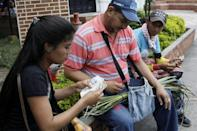 Genesis Materan (L) counts Colombian pesos as she sells vegetables and fruits bought in Venezuela to a customer in Cucuta, Colombia December 15, 2017. REUTERS/Carlos Eduardo Ramirez