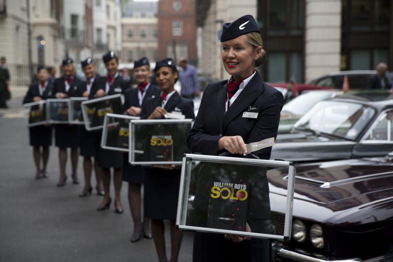 """Flight attendants pose for photographers with copies of the new James Bond novel """"Solo"""" during a launch photocall outside the Dorchester Hotel in London, Wednesday, Sept. 25, 2013. """"Solo"""" is set in 1969 and takes the suave British spy, 45 years old and feeling his age, from London's plush Dorchester Hotel to a war-torn West African country and to Washington. (AP Photo/Matt Dunham)"""