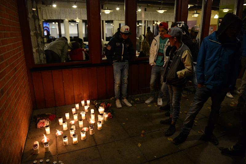 People stand next to candles at a makeshift memorial site at a school in Trollhattan, southwestern Sweden, on October 22, 2015, where a masked man armed with a sword attacked students and staff members (AFP Photo/Jonathan Nackstrand)
