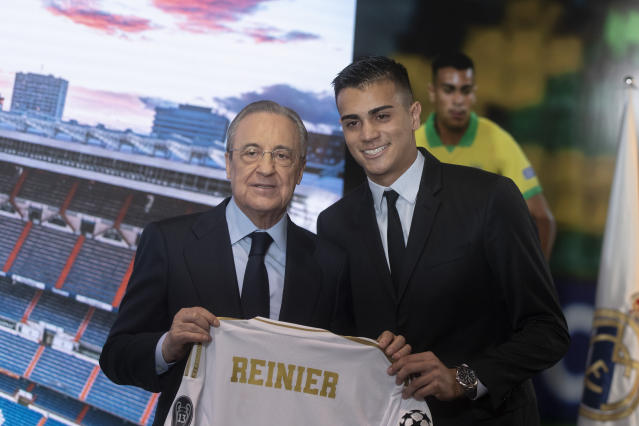 Brazilian player Rainier, right, holds up his new shirt next to club president Florentino Perez during his official presentation after signing for Real Madrid at the Santiago Bernabeu stadium in Madrid, Spain, Tuesday, Feb. 18, 2020. (AP Photo/Paul White)