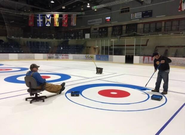 Goodyear, left, and a coworker prepare the ice for curling.