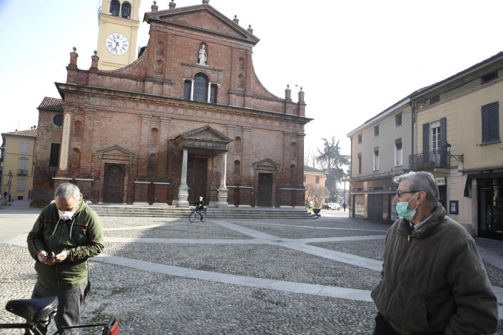 People wear masks as they stand in front of the San Biagio church in Codogno, near Lodi, Northern Italy, Saturday, Feb. 22, 2020. A dozen towns in northern Italy are on effective lockdown after the new virus linked to China claimed a first fatality in Italy and sickened an increasing number of people. The secondary contagions have prompted local authorities in towns of Lombardy and Veneto to order schools, businesses, and restaurants closed, and to cancel sporting events and Masses. (AP Photo/Luca Bruno)