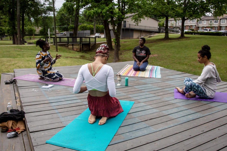 Jamilah Shakir, left, leads a group of women through yoga excercises on Wednesday, April 29, 2020, in Atlanta. Shakir says her family and friends have chosen to respect social distancing during Ramadan. Like many Muslims this year, she will also be missing the special Ramadan taraweeh prayers at the mosque and the imam reciting verses from the Quran. But she looks for the blessings. (AP Photo/Ron Harris)