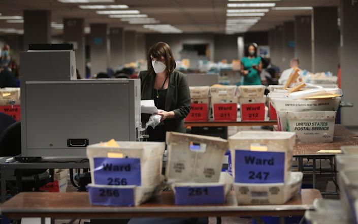 Claire Woodall-Vogg, executive director of the Milwaukee election commission collects the count from absentee ballots from a voting machine - Getty Images North America