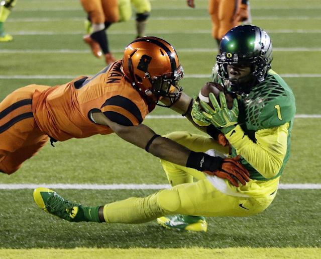 Oregon receiver Josh Huff, right, hauls in the game-winning touchdown against Oregon State defender Tyrequek Zimmerman during the second half of an NCAA college football game in Eugene, Ore., Friday, Nov. 29, 2013. Oregon won 36-35. (AP Photo/Don Ryan)