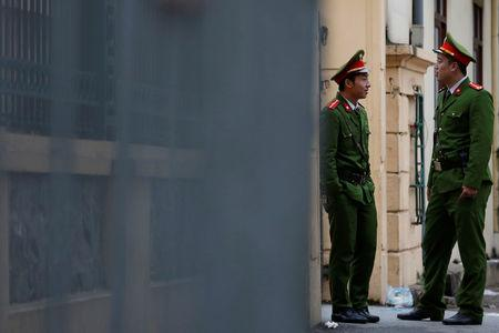 Vietnamese policemen stand guard outside the court in Hanoi