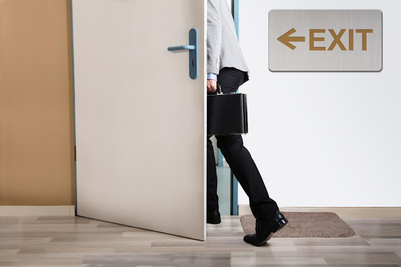 Man with a briefcase walking out a door marked by an exit sign