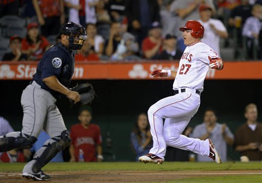 Los Angeles Angels' Mike Trout, right, scores on a single by Albert Pujols as Seattle Mariners catcher Miguel Olivo waits for a throw during the first inning of their baseball game, Tuesday, Sept. 25, 2012, in Anaheim, Calif. (AP Photo/Mark J. Terrill)