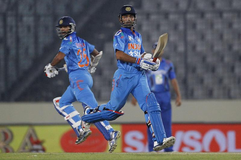 India's Ajinkya Rahane, right, and Shikhar Dhawan run between the wickets during their match against Afghanistan in the Asia Cup one-day international cricket tournament in Dhaka, Bangladesh, Wednesday, March 5, 2014. (AP Photo/A.M. Ahad)