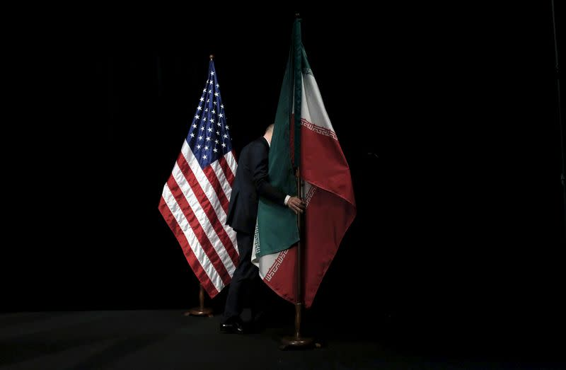 A staff member removes the Iranian flag from the stage after a group picture with foreign ministers and representatives during the Iran nuclear talks at the Vienna International Center in Vienna