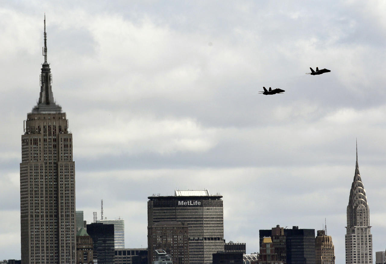 Two US Navy Flight Demonstration Squadron jets, better known as Blue Angels, seen from Liberty State Park in Jersey City, N.J., execute a survey flight over New York City, including the Empire State Building, left, and the Chrysler Building, right, Monday, April 2, 2012. The two F/A-18 Hornet Fighter Jets flew practice runs to familiarize and evaluate a potential flight course for the upcoming US Navy War of 1812 commemoration during this year's Fleet Week celebration in May. (AP Photo/Julio Cortez)
