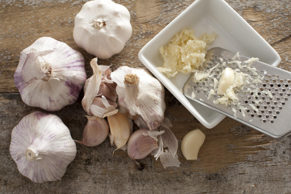 Four garlic bulbs beside a white square bowl holding shredded cloves and stainless steel grater