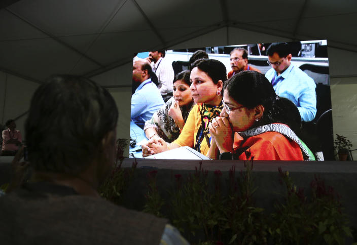 Live pictures of Indian Space Research Organization (ISRO) scientists reacting are displayed on a big screen at their Telemetry, Tracking and Command Network facility in Bangalore, India, Saturday, Sept. 7, 2019. India's space agency says it has lost communication with its unmanned spacecraft that was set to touch down Saturday on the moon's south pole. (AP Photo/Aijaz Rahi)