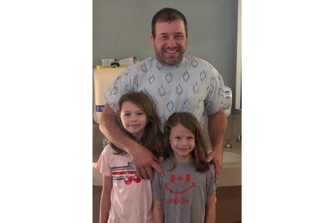 This undated photo provided by Roush Racing shows NASCAR driver Ryan Newman and his daughters, Brooklyn Sage, left, and Ashlyn Olivia, at Halifax Medical Center in Daytona Beach, Fla. Newman is fully alert, walking around the hospital and joking with staff two days after his frightening accident on the final lap of the Daytona 500 auto race. Roush Fenway Racing said Wednesday, Feb. 19, 2020, the 42-year-old continues to show great improvement. (Roush Racing via AP)