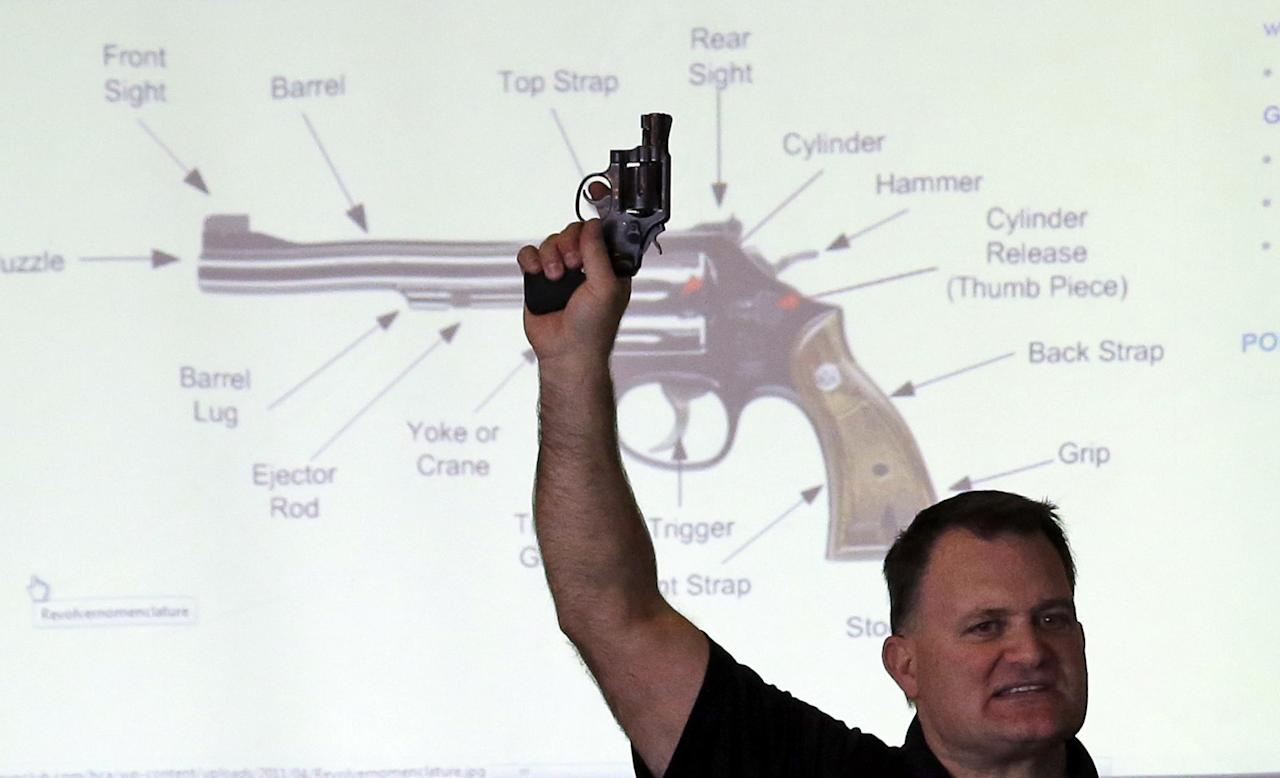 Clark Aposhian, President of Utah Shooting Sport Council, holds a pistol during concealed weapons training for 200 Utah teachers Thursday, Dec. 27, 2012, in West Valley City, Utah. The Utah Shooting Sports Council offered six hours of training in handling concealed weapons in the latest effort to arm teachers to confront school assailants. (AP Photo/Rick Bowmer)