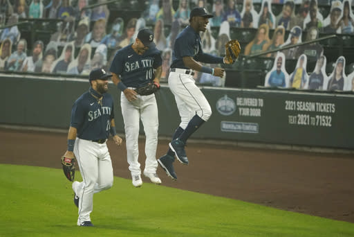 Seattle Mariners center fielder Kyle Lewis, right, leaps with left fielder Jose Marmolejos, left, near right fielder Tim Lopes (10) after making a leaping catch of a deep fly ball hit by Oakland Athletics' Ramon Laureano with two outs and the bases loaded during the first inning of the second baseball game of a doubleheader, Monday, Sept. 14, 2020, in Seattle. (AP Photo/Ted S. Warren)