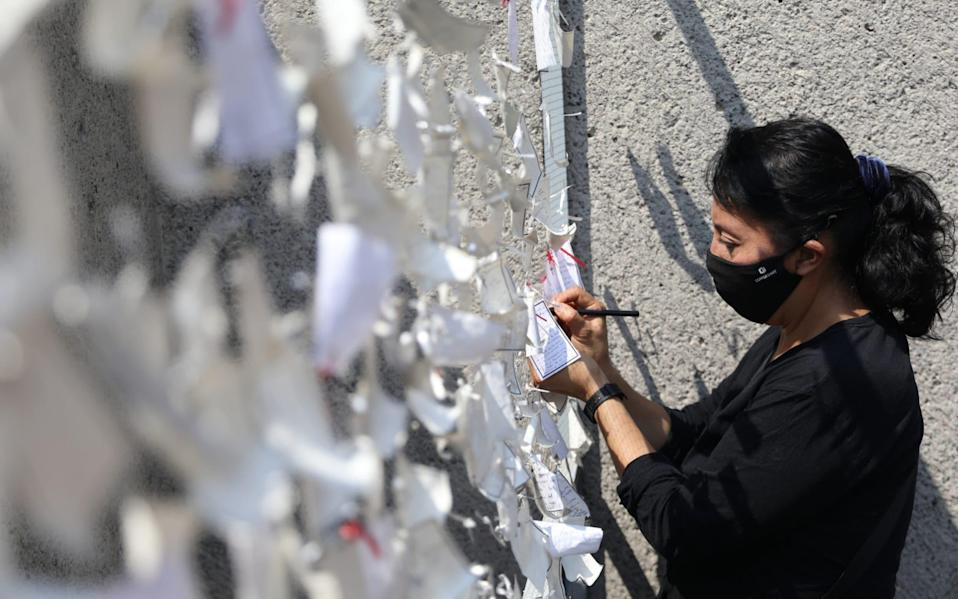 A woman places a message dedicated to people who died with Covid-19, on a wall at the Basilica of Guadalupe in Mexico City - Sashenka Gutierrez/EPA-EFE/Shutterstock