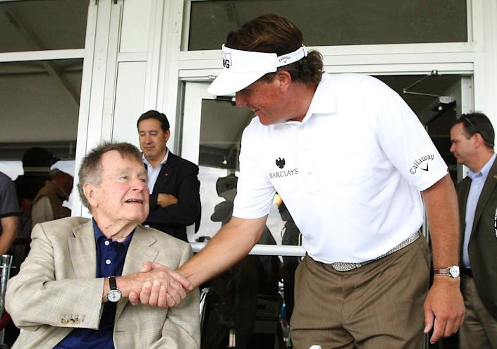 <p>Phil Mickelson visits with former President George H.W. Bush after completing the third round of the Houston Open golf tournament on March, 30, 2013, in Humble, Texas. (Photo: Patric Schneider/AP) </p>
