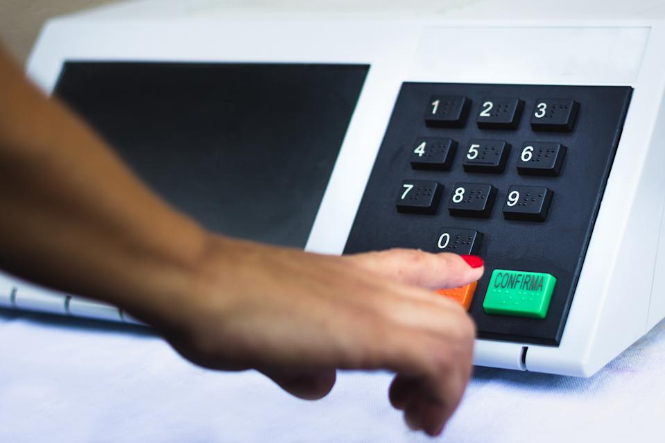 In this photo illustration a woman simulates a vote in the electronic ballot box used in the elections of Brazil.