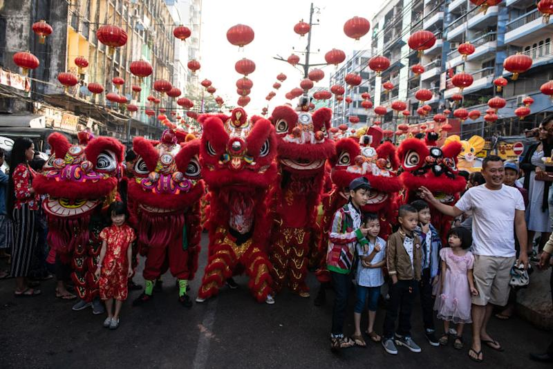 Children take a photograph wiht lion dancers during a ceremony to mark the first day of the Lunar New Year in Yangon's Chinatown on January 25, 2020. Chinese New Year, also known as Lunar New Year or Spring Festival is most important festival for Chinese people. (Photo by Shwe Paw Mya Tin/NurPhoto)