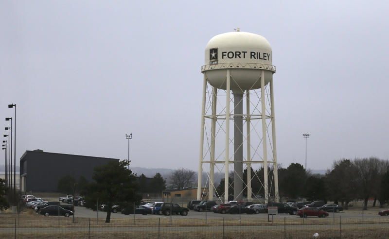 FILE - In this Feb. 9 2015 file photo, vehicles park around a water tower at Fort Riley, Kan. Prosecutors say a U.S. Army soldier shared bomb-making instructions online and also discussed killing activists and bombing a news network. (AP Photo/Orlin Wagner, File)