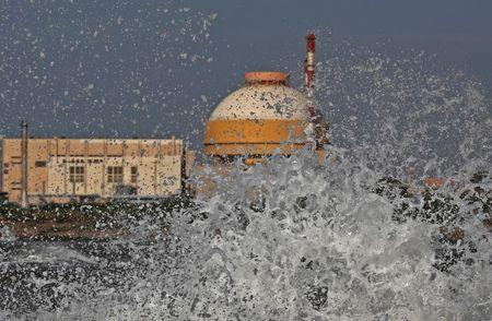 Sea waves hit the rocks as Kudankulam nuclear power project plant is seen in the background