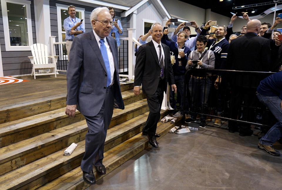 Berkshire Hathaway CEO Warren Buffett (L) walks with Kevin T. Clayton, CEO of Berkshire Hathaway subsidiary Clayton Homes, out of one of the company's houses prior to the Berkshire annual meeting in Omaha, Nebraska May 2, 2015.  Billionaire investor Buffett on Saturday defended his Clayton Homes unit against accusations that the manufactured home seller had preyed on lower-income purchasers with its lending practices. REUTERS/Rick Wilking