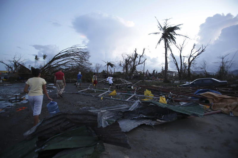 """Residents walk by debris after powerful Typhoon Haiyan slammed into Tacloban city, Leyte province, central Philippines on Saturday, Nov. 9, 2013. The central Philippine city of Tacloban was in ruins Saturday, a day after being ravaged by one of the strongest typhoons on record, as horrified residents spoke of storm surges as high as trees and authorities said they were expecting a """"very high number of fatalities."""" (AP Photo/Aaron Favila)"""