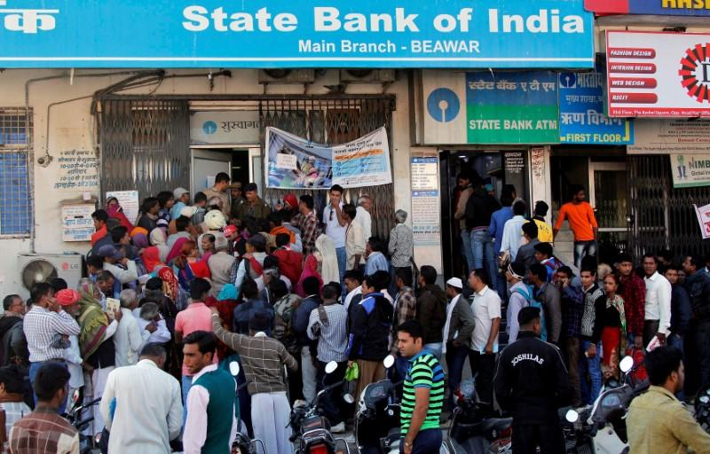 FILE PHOTO: People crowd the entrance of the State Bank of India branch to deposit or exchange their old high denomination banknotes in Beawar city