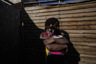 """Develine, born in the Republic Dominican to Haitian parents, holds her two-year-old, Chilean-born sister Cataleya, outside their home where they live with their mother Magdaline Afred, who has permanent Chilean residency, in Santiago's Dignidad camp set up by migrants in Chile, Thursday, Sept. 30, 2021. There are 180,000 Haitians in Chile, of whom """"almost 70,000 reside in the country permanently,"""" said deputy interior minister Juan Francisco Galli. (AP Photo/Esteban Felix)"""