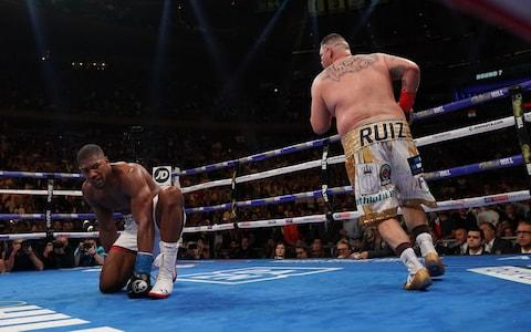 Anthony Joshua kneels on the canvas after being knocked down by Andy Ruiz - Credit: afp